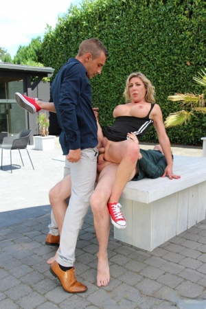 Blonde chick Nikky Clarisse does a DP on a patio sofa in red sneakers