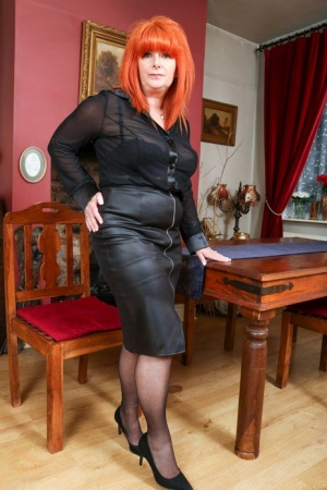 Older redhead unzips a leather skirt before showing her natural tits and pussy