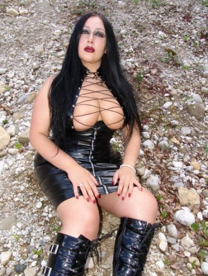Goth woman Lady Angelina models outdoors in a latex dress and knee-high boots