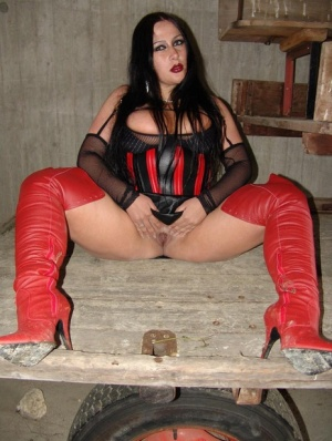 Goth girl Lady Angelina poses in latex clothing inside a farm storage building
