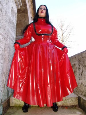 Goth woman Lady Angelina models a red latex dress during non-nude action
