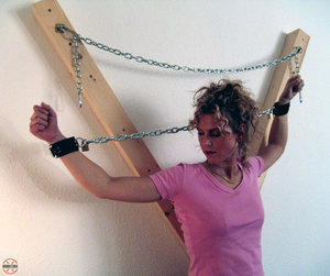 Clothed female Blonde Lea is attached to a St Andrews Cross