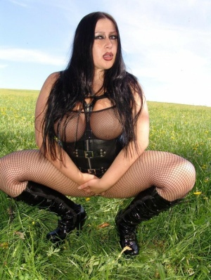 Busty girl with long brunette hair models in a field in mesh attire and boots 79378572