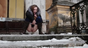 Clothed redhead Vika squats for a pee on the snow-covered steps of a church