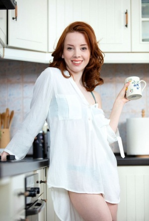 Pale redhead Lottie Magne touches her naked teen pussy in the kitchen