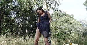 Brunette chick Sasha squats for a pee in front of a birch tree in the country