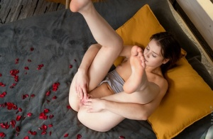 College girl Matty finger spreads her pink pussy on a bed amid rose petals