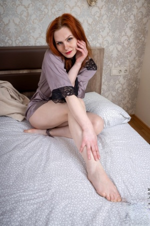 Redheaded housewife Selena removes her robe for her first nude poses on a bed