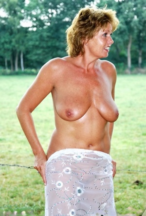 Older amateur with short red hair gets naked by a barbed wire fence