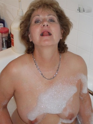 Older amateur Busty Bliss licks her lips during a playful bubble bath 83007363