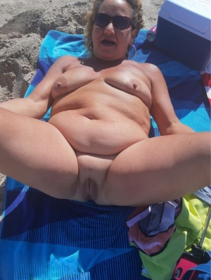 Older amateur Debbie Delicious smokes while sunbathing in the nude on a beach