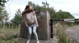 Clothed girl Sasha squats for a piss behind a concrete block on a path