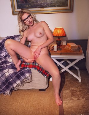 Young blonde Lilly Bella doffs clothing and glasses before a nude finger fuck
