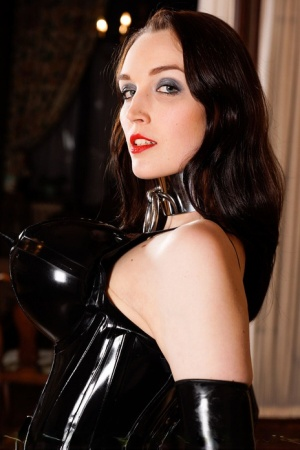 Fetish model Dutch Dame poses in a double-D rubber suit and a slave collar