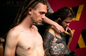 Dreadlock sporting individuals partake in femdom play on a wooden bench