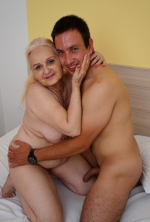 Blonde granny kisses her toy boy after they fuck on top of a bed
