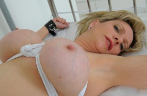 Busty older UK blonde Lady Sonia tied to a bed in nylons and garters