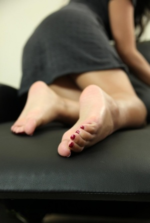 Asian female from the UK Ayla Sky removes nylons before playing with her feet