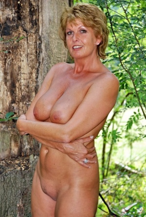 Mature lady displays her great body while naked up against a tree 37922722