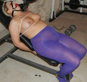 Chubby blonde sports a ball gag while topless  restrained in purple pantyhose