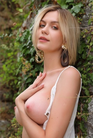 Beautiful blonde gets completely naked outside a stone dwelling