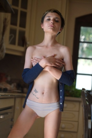 Short haired girl Caterina Foxy gets mostly naked while in her kitchen