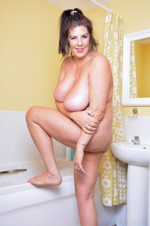 Thick British woman Lulu Lush plays with her huge boobs while taking a bath