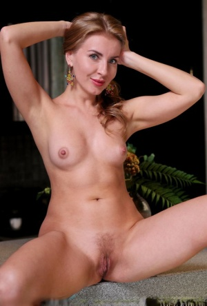 Young blonde Bjorg Larson removes a yellow dress to model in the nude
