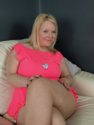 Thick amateur Sindy Bust teases on leather furniture in a short pink dress