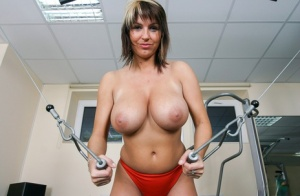 Big titted chick Kora Kryk disrobes to a thong while working out in a gym