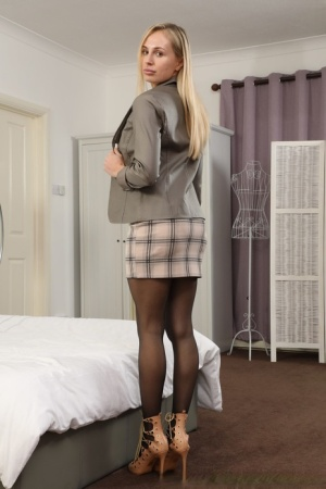 Tall blonde Cassie B places hands over her firm tits in nylons and garters
