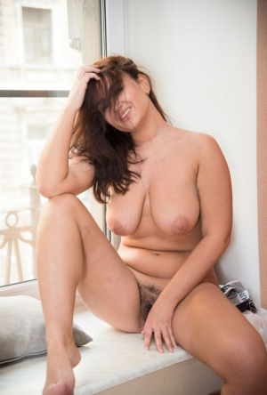 Young and busty brunette Sanita showcases her natural pussy by a window