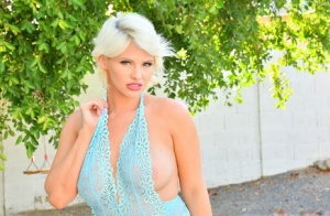 Platinum blonde Charli sets her big boobs free on a poolside patio