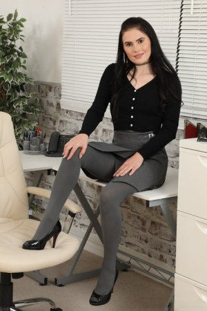Brunette secretary Deannah stands topless in grey pantyhose and heels