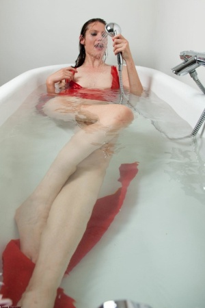 Leggy brunette works free of red latex clothing while being drowned in a tub