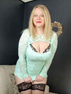 Chubby blonde Sindy Bust strips down to her stockings and heels by herself
