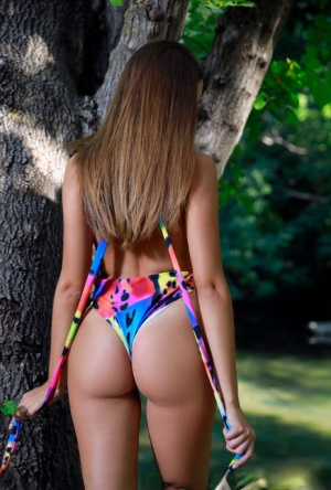 Young brunette Rosalina removes a bathing suit to pose nude next to a creek