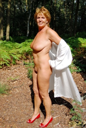 Older redhead removes a robe to stand naked in red heels while in the woods