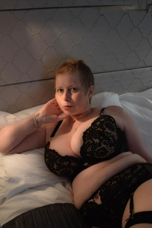 Older plumper Posh Sophia exposes her large boobs and shaved pussy on a bed