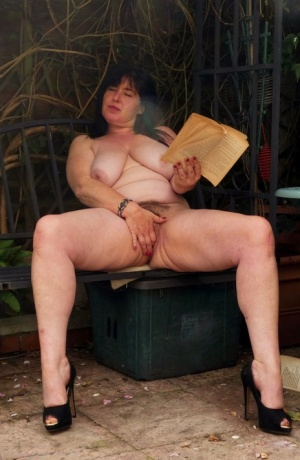 Busty British woman Juicey Janey masturbates while reading a book on a patio
