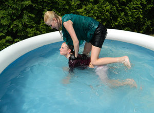 Clothed lesbians get soaking wet after getting into an above-ground pool