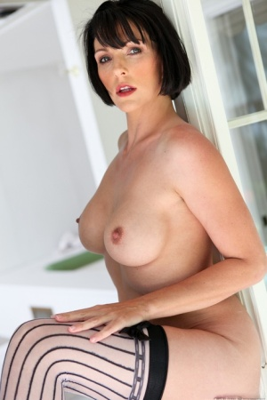Brunette MILF Roxanne Hall struts about in sexy stockings and high heels