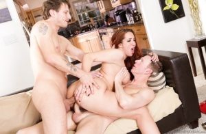Busty redhead Kelly Divine has her hair pulled during a hard DP