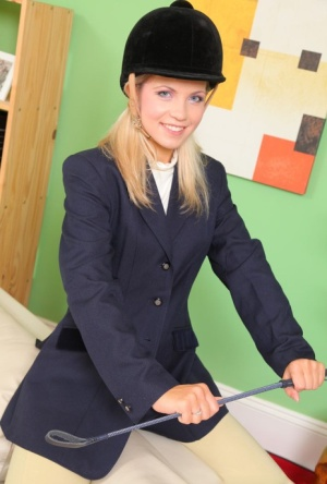 Young blonde Jenni P removes riding attire to model topless in pantyhose
