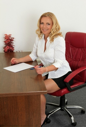 Mature office worker Britney reveals her big nipples and spreads at her desk