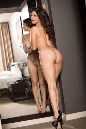 Indian girl Sunny Leone frees her big tits in a mirror as she removes lingerie