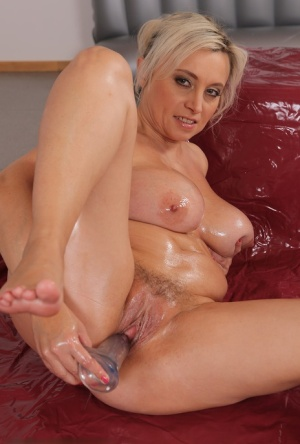 Horny mature Sindy Huga strips to oil her huge big tits  toy with dildo naked