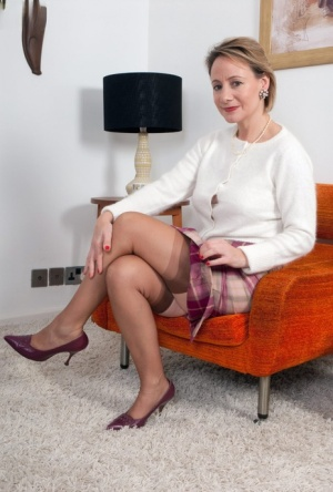 Classy woman Tiffany T parts her pussy attired in retro nylons and garters