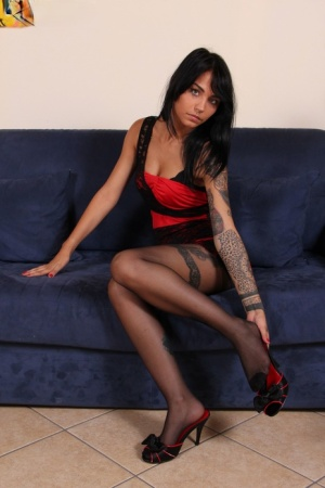 Tattooed girl with black hair frees stocking clad feet from shoes on a sofa