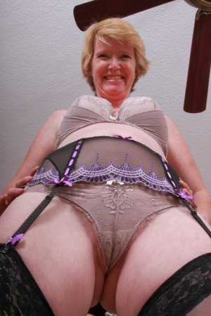 Horny granny laughingly displays the wet cameltoe under her sheer undies